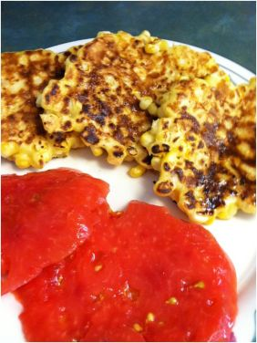Shucking Fritters on plate with tomatoes